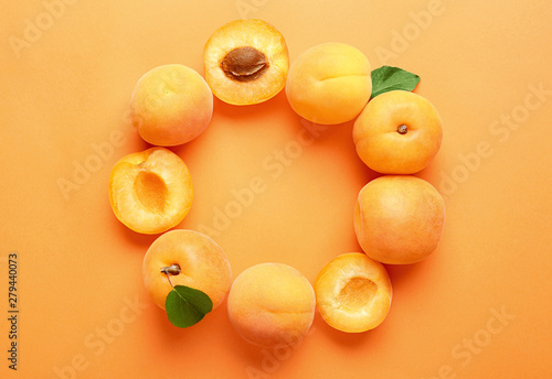 Fotografía Delicious ripe sweet apricots on orange background, flat lay