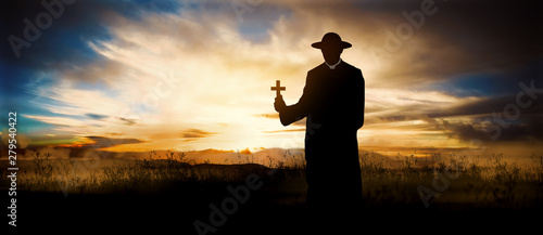Fotografia, Obraz priest on the hill at sunset with the cross