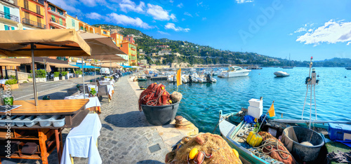 Fotografie, Obraz Street scene with cafe and fishing boat in resort town Villefranche-sur-Mer