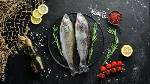 Photo Raw fish trout on a plate. Top view. Free space for your text.