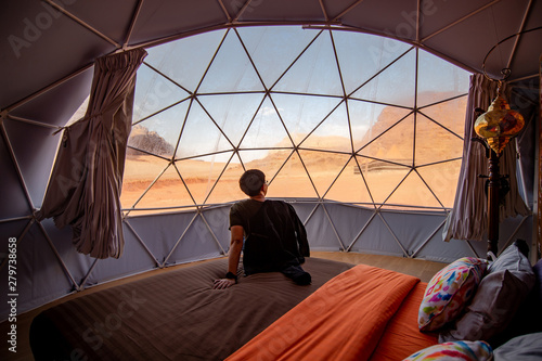 Leinwand Poster Asian tourist man sitting on the bed in dome tent looking outside at Wadi Rum desert, famous natural attraction in Jordan