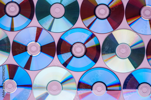 CD DVD compact disc disk dispersion refraction reflection of light colors texture on pink background #279882627