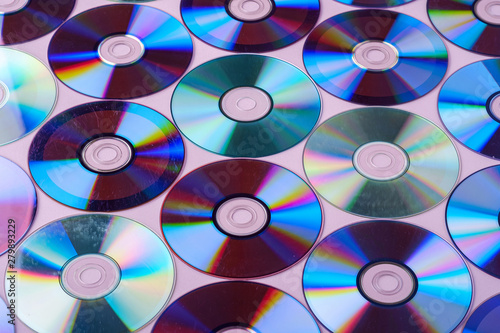 CD DVD compact disc disk dispersion refraction reflection of light colors texture on pink background #279893229