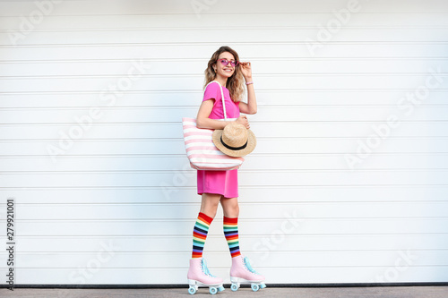 Foto Happy young woman with retro roller skates near white garage door