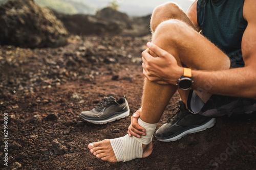 Man bandaging injured ankle Fototapete