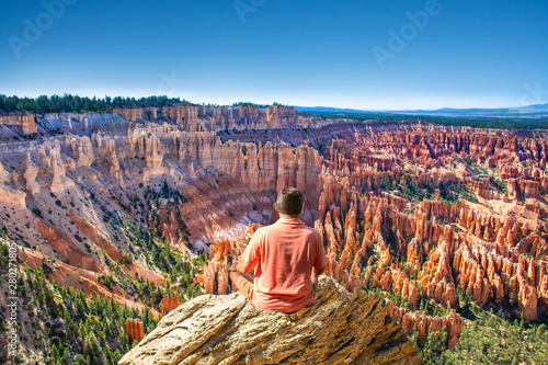 Man sitting on top of the mountain looking at beautiful view Fototapet