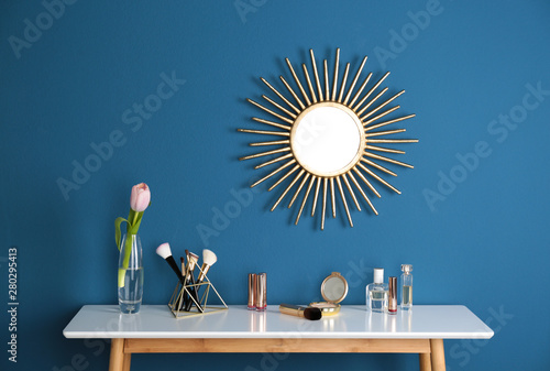 Obraz na plátně Dressing table with spring flower and makeup products at blue wall