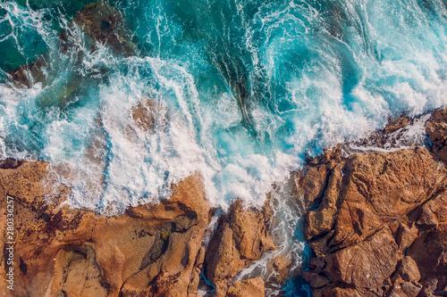 Obraz na płótnie Coast of desert island with blue turquoise water beats on rocky reef