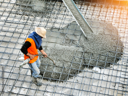 Stampa su Tela Top view of builders in orange shirt pouring concrete works on the construction