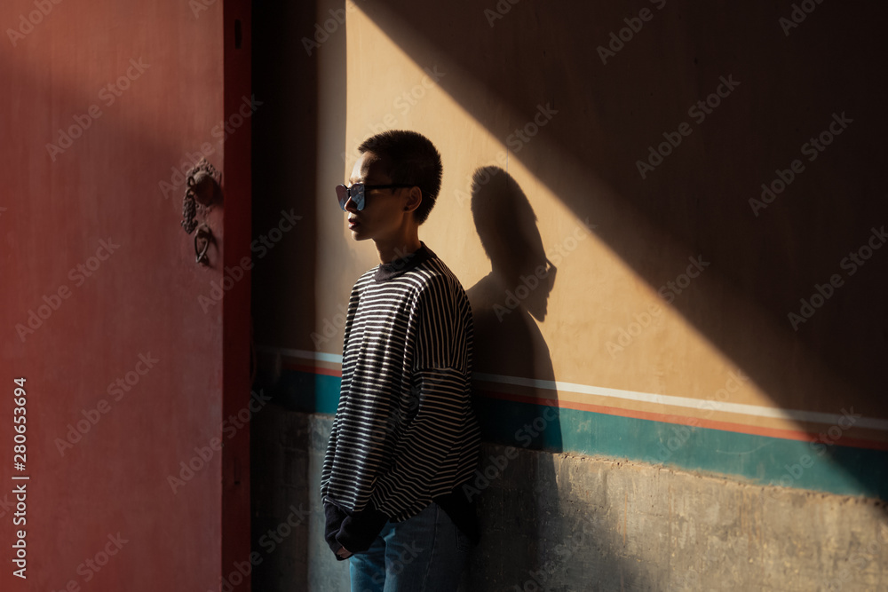 Woman wearing sunglasses leaning on wall