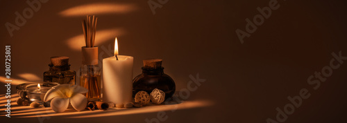 Beautiful spa composition with candles, frangipani flower, oil flasks and other decor elements.