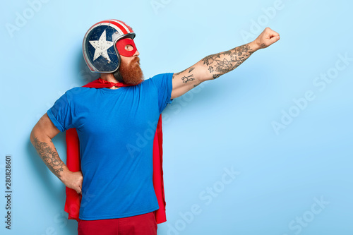 Stampa su Tela Profile shot of serious bearded man makes flying gesture, looks into distance, w