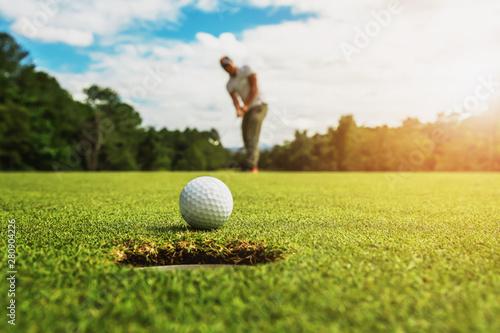 golf player putting golf ball into hole