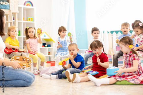 Photo Group of kindergarten children play with musical toys