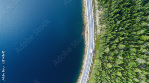 Fotografia Aerial view of white caravan car driving on country road in forest near lake with beautiful blue water