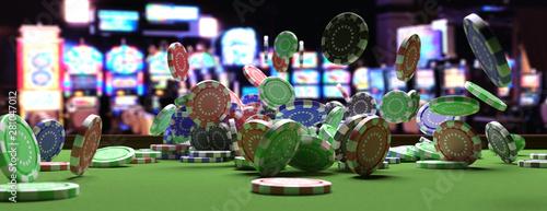 Photo Poker chips falling on green felt roulette table, blur casino interior background