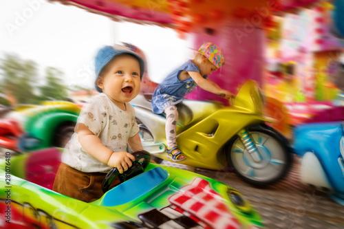 cheerful children in carousel at amusement park Fototapete