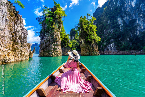 Carta da parati Beautiful girl sitting on the boat and looking to mountains in Ratchaprapha Dam at Khao Sok National Park, Surat Thani Province, Thailand
