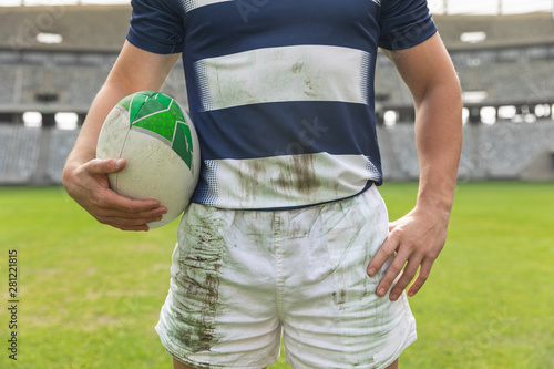 Male rugby player standing with rugby ball in stadium