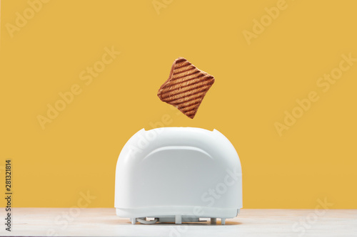 Fotografie, Obraz Roasted toast bread popping up of toaster with yellow wall