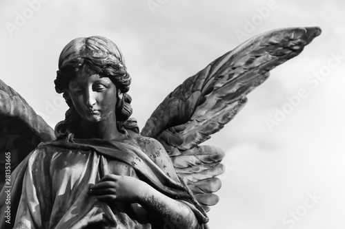 Photo Sad angel sculpture with open long wings across the frame against a bright white sky