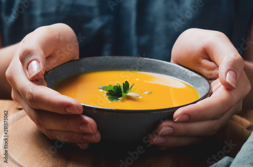 Canvas Print Female hand holding a  bowl with pumpkin cream soup