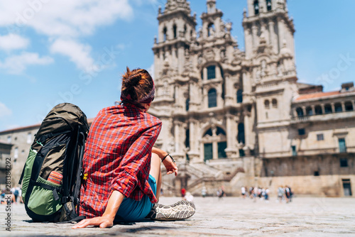 Canvas Print Woman backpacker piligrim siting on the Obradeiro square (plaza) in Santiago de