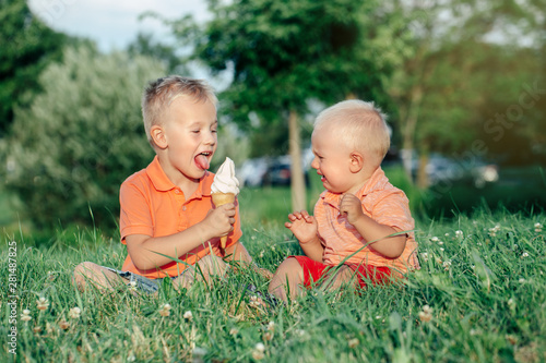Two Caucasian funny children boys siblings sitting together eating sharing one ice-cream Fototapeta