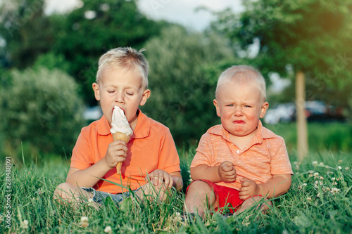 Two Caucasian funny children boys siblings sitting together eating sharing one ice-cream Poster Mural XXL