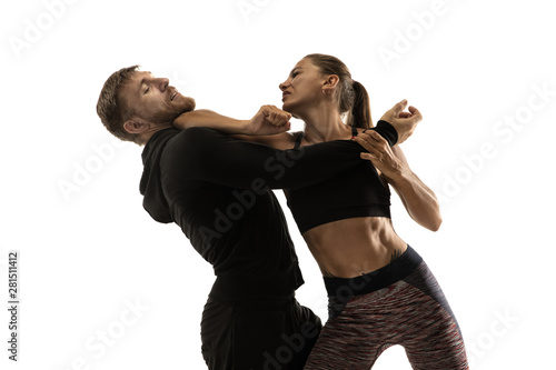 Fotografiet Man in black outfit and athletic caucasian woman fighting on white studio background