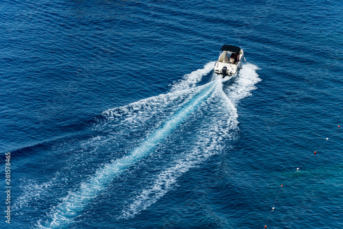 Fotografie, Obraz White motorboat in motion with wake in the blue Mediterranean sea photographed from above