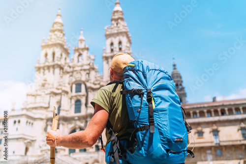 Photo Backpacker man pilgrim looking at Santiago de Compostela Cathedral standing on the Obradeiro square (plaza) - the main square in Santiago de Compostela as a end of his Camino de Santiago pilgrimage