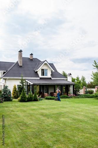 Fotografija a man cutting grass of a private house in spring