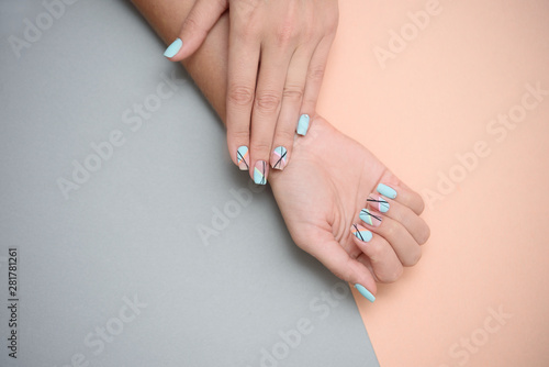 Beautiful female manicure on a pastel color background.