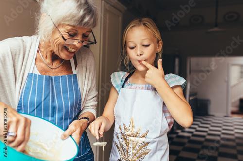 Fototapeta Grandmother and kid having fun making cake in kitchen
