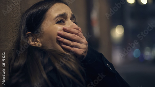 Foto Shocked robber victim crying at night street, panic attack, psychological trauma