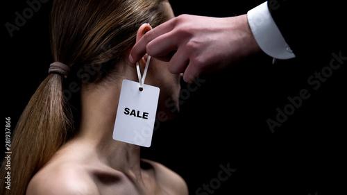 Fotografia Male hand putting sale tag on female ear, illegal women trafficking, sex slavery