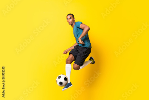 Fototapeta Afro American football player man over isolated yellow background