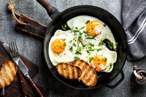 Fényképezés fried eggs in a cast iron pan top view