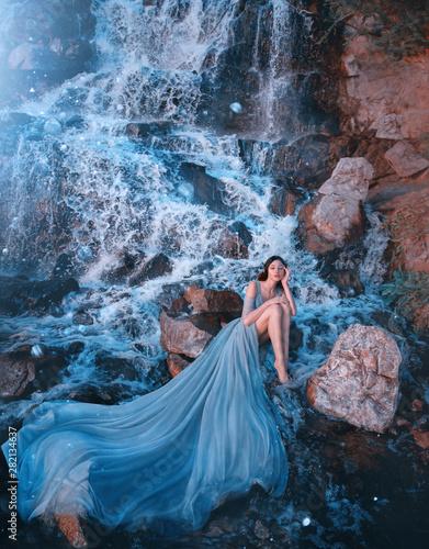 Fototapeta lost princess sitting on wet stones near gorgeous high waterfall, lady in blue d