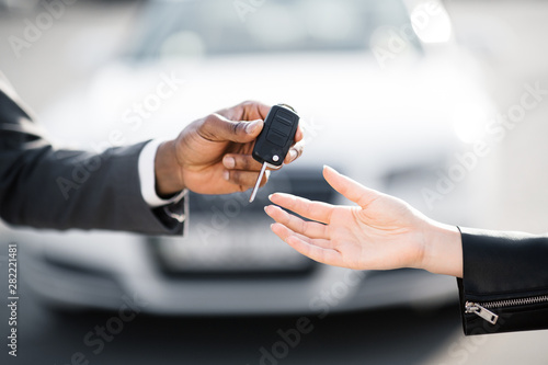 Car salesman handing over keys for new car to young woman