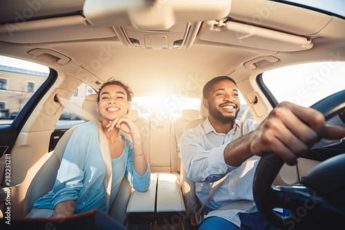 Tableau sur Toile Enjoying travel. Excited african couple driving car