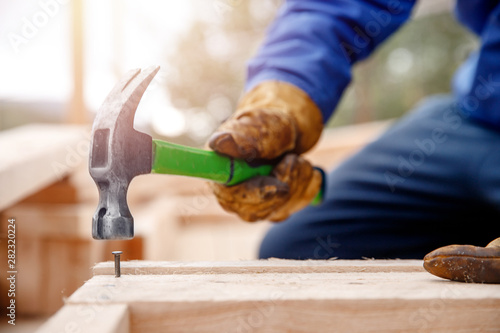 Male builder in yellow gloves hammer nail into wooden structure. Construction concept
