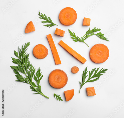 Cut carrot and leaves isolated on white, top view Fototapete