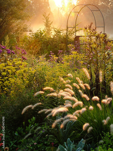 Large country garden with flowers and ornamental grasses and an arbor (arch) bac Fototapet