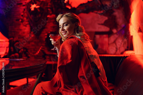 Canvas Print Picture of happy blonde in red jacket looking at camera with cocktail in her han