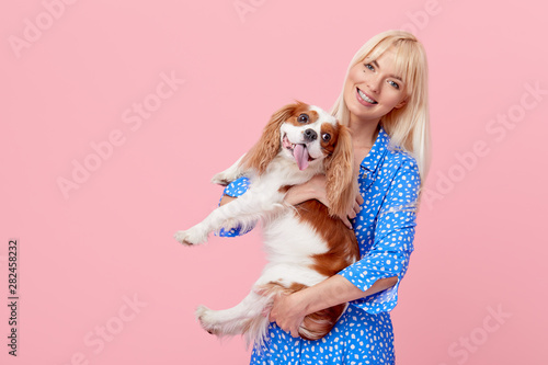 Canvas-taulu Portrait of smiling young blond woman in summer hat embracing king Charles spaniel dog
