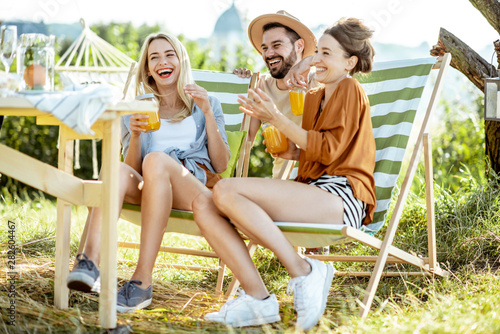 Young friends talking and having fun, while sitting together with summer drinks Poster Mural XXL