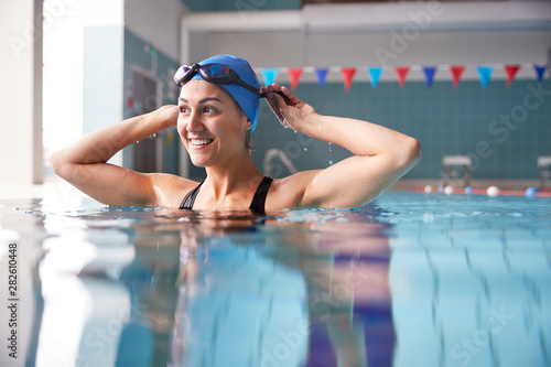 Fotografie, Obraz Female Swimmer Wearing Hat And Goggles Training In Swimming Pool