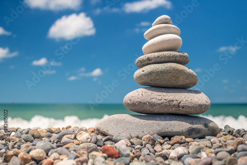 Photo pyramid of sea pebbles on the beach against the backdrop of the sea wave in sunny day
